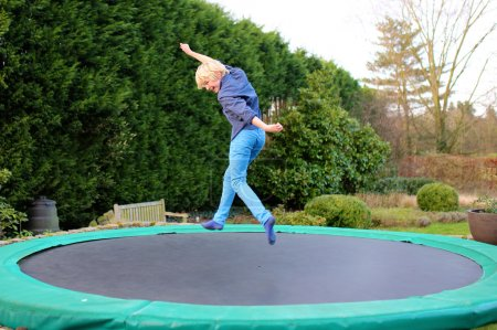 Happy boy jumping on trampoline