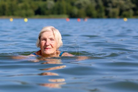 Senior woman swimming in the lake