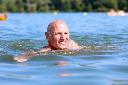 Senior man swimming in the lake