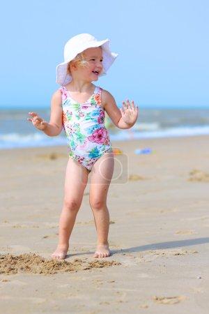 Happy toddler girl enjoying summer day on the beach
