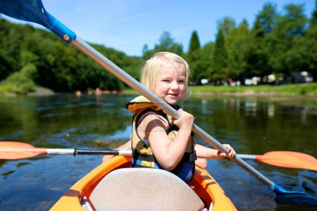 Active little girl kayaking on the river