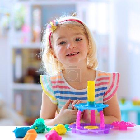Photo pour Petite fille d'âge préscolaire jouant avec la plasticine. Enfant heureux, adorable petite fille créative jouant avec la pâte, composé de modélisation coloré, assis à la table blanche dans une pièce ensoleillée lumineuse à la maison ou à la maternelle - image libre de droit