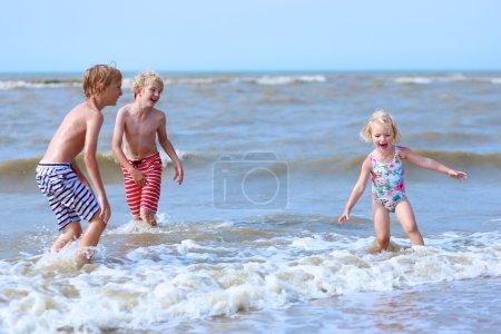 Happy children splashing in the sea