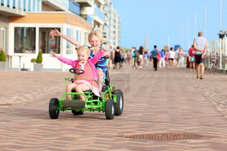 Kids riding pedal car on the beach