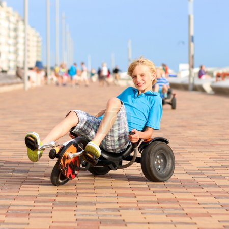 Teenage boy riding pedal car along the beach