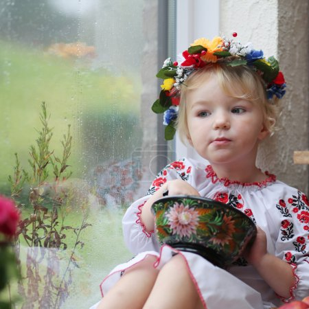 Photo for Cute little patriotic child, blonde curly toddler girl in traditional ukrainian dress and wreath sitting indoors next to a big window with garden view eating from painted wooden plate - Royalty Free Image