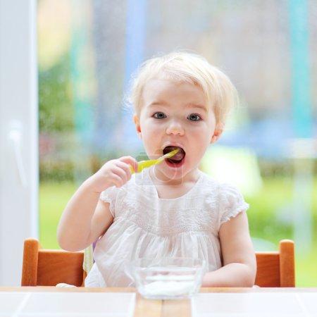 Toddler girl eating yogurt from spoon