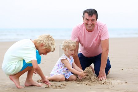 Father with kids playing on the beach