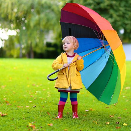 Little girl walking with colourful umbrella