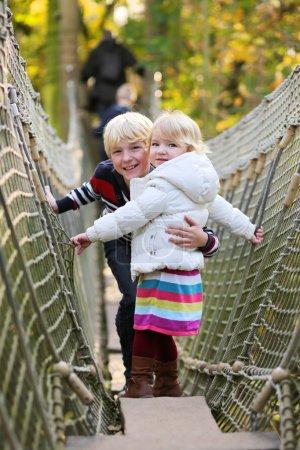 Photo pour Groupe d'enfants blonds heureux, fille d'âge préscolaire avec son frère adolescent s'amusant à l'aire de jeux sur une journée ensoleillée escalade sur le pont dans le parc d'aventure - image libre de droit