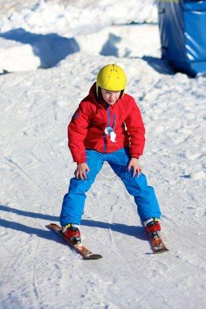 Happy boy enjoying ski school in Alpine resort