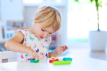 Preschooler girl playing with plasticine