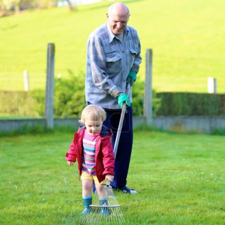 Grandfather with granddaughter working in the garden
