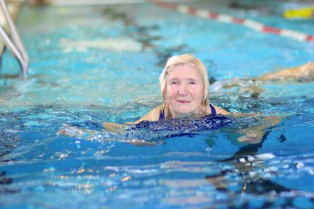 Photo for Happy healthy senior woman enjoying sportive lifestyle swimming in the pool - active retirement concept - Royalty Free Image