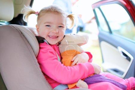 Happy toddler girl enjoying trip in the car