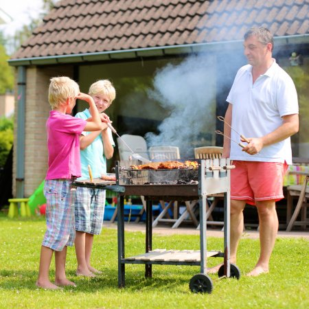 Father and sons preparing barbecue for summer party