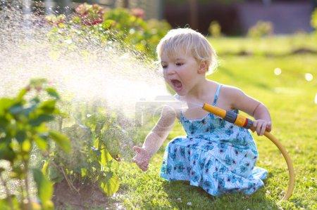 Photo pour Petit enfant, adorable petite fille blonde, arrosant les plantes, belles fleurs d'hortensia, du jet de tuyau dans le jardin à l'arrière-cour de la maison lors d'une soirée d'été ensoleillée - image libre de droit