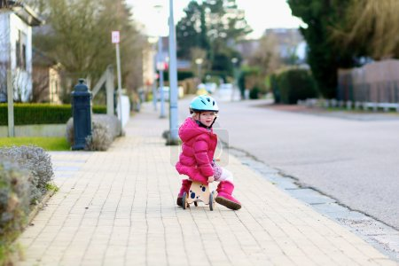 Little child playing on the street riding tricycle