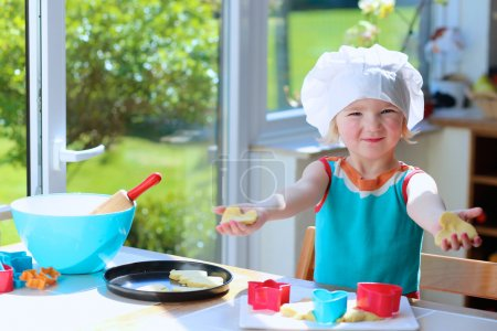 Photo pour Petit enfant heureux, fille adorable d'enfant en bas âge dans le chapeau blanc de chef aidant la mère cuisant la pâte delisious dans la cuisine - image libre de droit