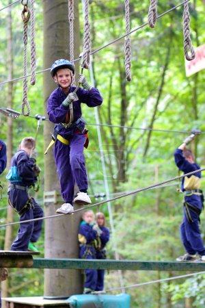 Happy school boy climbing in adventure park