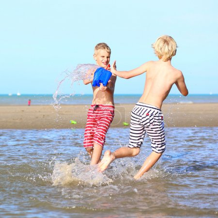 Two active boys playing on the beach
