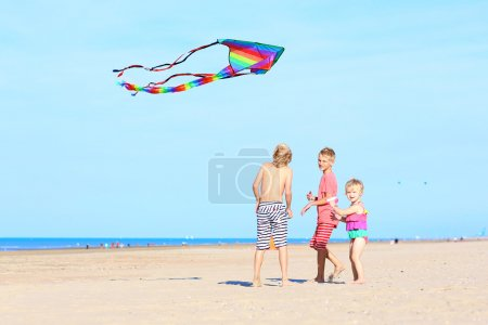Happy children playing with kite on the beach