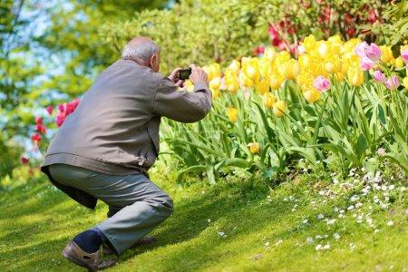 Happy senior man enjoying flowers park