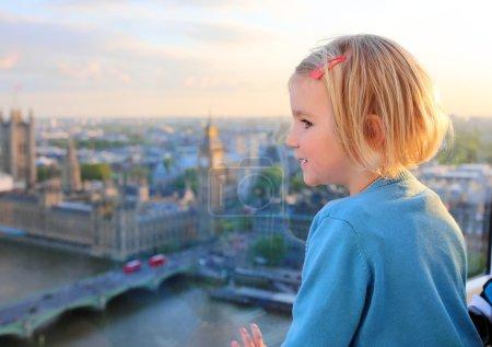 Photo pour Famille avec de jeunes enfants appréciant le voyage au R-U. Gosses regardant par la fenêtre de la roue de oeil de Londres. Belle vue sur la partie sud de Londres : paysage urbain, abbaye de Westminster, Big Ben et Tamise - image libre de droit