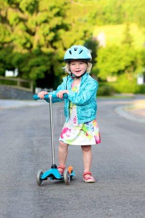 Preschooler girl riding scooter on