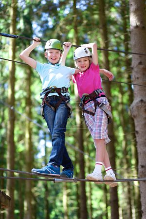 Two active school boys climbing in adventure park