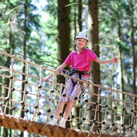 Photo pour Enfant heureux, adolescent en bonne santé qui profite d'une activité dans un parc d'aventure d'escalade un jour d'été - image libre de droit