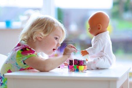 Photo pour Petit enfant, fille mignonne d'enfant en bas âge ayant l'amusement jouant à la maison avec le vernis à ongles coloré faisant la manucure et peignant des ongles à sa poupée - image libre de droit