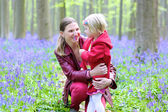 Mother and daughter playing and hugging in the forest