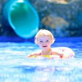 Laughing little girl swimming in the pool