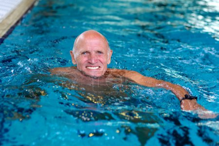 Active senior man swimming in the pool
