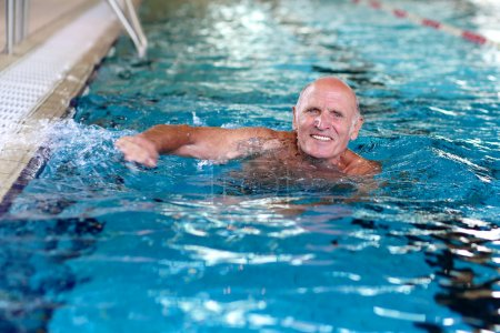 Photo for Healthy senior man swimming in the pool. Happy pensioner enjoying sportive lifestyle. Active retirement concept. - Royalty Free Image