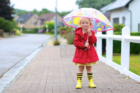 Photo for Happy little child, adorable blonde curly toddler girl wearing red duffle coat, bright yellow wellies and holding colorful umbrella walking on the street on a chilly autumn or spring day - Royalty Free Image