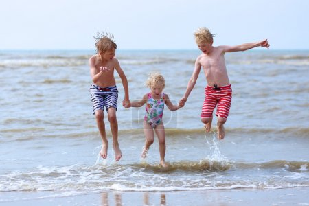 Kids having fun on the beach jumping over the waves