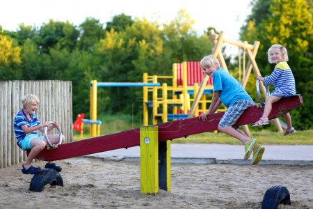 Photo for Happy kids enjoying active summer vacation. Group of happy children, blond cute toddler girl and two schoolboys, having fun outdoors swinging on playground in the park on a sunny day - Royalty Free Image