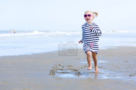 Little girl playing on the beach at summer