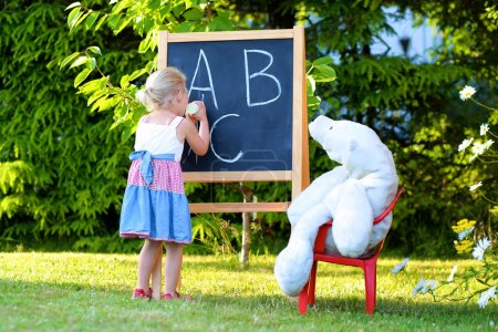Photo for Little preschooler girl excited to go back to school. Cute toddler playing teacher role game outdoors. Happy kid leaning letters at kindergarten. Children education concept. - Royalty Free Image