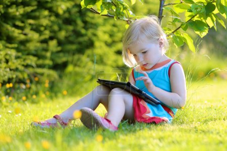 Toddler girl using tablet pc outdoors