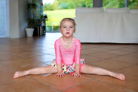 Little gymnast girl training at home