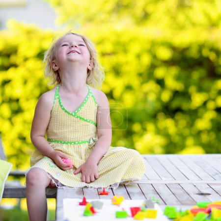 Photo for Little girl playing with plasticine and colorful forms. Happy child, adorable toddler girl creating from modeling compound dough, sitting outdoors in the garden on sunny summer day - Royalty Free Image