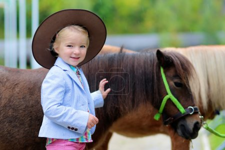 Happy little girl and her pony