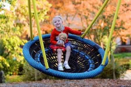 Photo pour Petit enfant riant qui s'amuse au terrain de jeu. Petite fille blonde mignonne balançant dans le parc. Enfants heureux jouant en plein air le jour ensoleillé d'automne . - image libre de droit