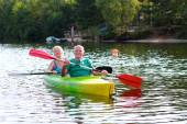 Healthy seniors kayaking on the river