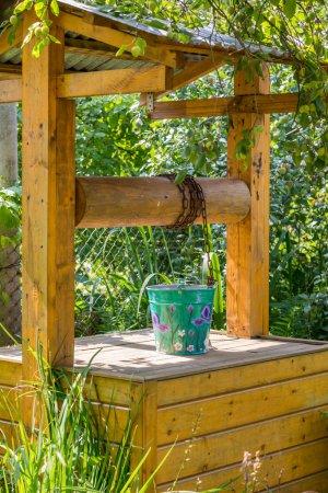 Photo pour Seau en métal peint sur un puits de village en bois - image libre de droit