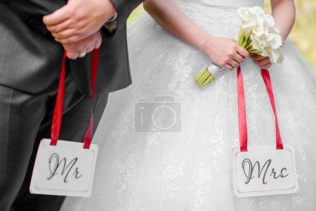 Photo pour Mariée et marié tenant les étiquettes Mr & Mrs dans leurs bras - image libre de droit