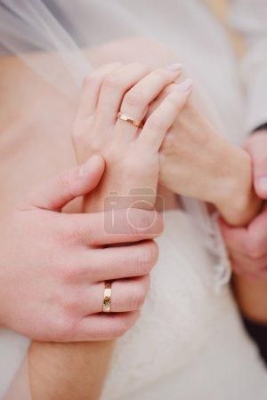 Photo pour Jeunes mariés tenant les bras serrés les uns des autres - image libre de droit